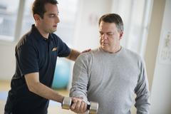USA, New Jersey, Jersey City, Fitness instructor assisting man using hand weight - stock photo