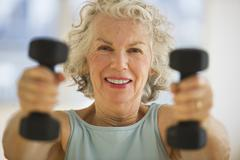 USA, New Jersey, Jersey City, Portrait of senior woman using hand weights at gym - stock photo