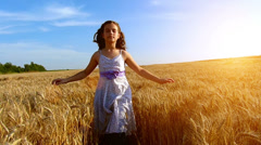 Little girl with arms outstretched in a wheat field Stock Footage