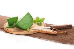 green gouda cheese on brown cutting board. - stock photo