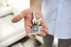 a man holds in his hand the keys of his house, indoor. - stock photo