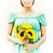 Stock Photo of Young woman holding sunflowers