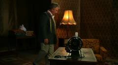 Pan shot of an old tailor seating on a chair and listening to the radio - stock footage