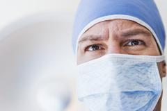 Male surgeon wearing surgical mask - stock photo