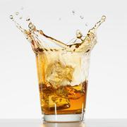 Studio shot of ice cubes splashing into glass of whiskey Stock Photos