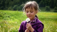 Shot of little girl blowing dandelion's blossom Stock Footage