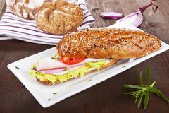 wholegrain baguette on white tray. - stock photo