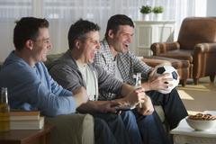USA, New Jersey, Jersey City, three men watching television - stock photo