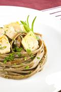 exquisite dining. pasta with artichoke. - stock photo