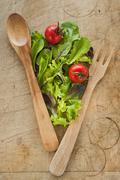Stock Photo of Salad leaves and wooden spoon and fork