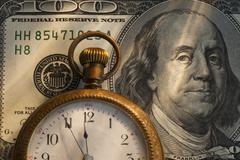 Pocket watch on one hundred dollar bill, studio shot Stock Photos