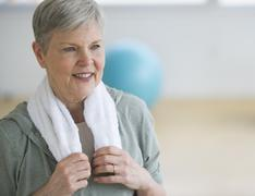 Smiling senior woman in gym - stock photo