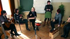 Right to left pan the group of people that are learning a new song Stock Footage