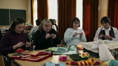 Teacher is demonstrating basics of knitting to the course participants - stock footage