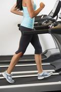 Low section of woman walking on treadmill - stock photo