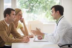 Couple receiving advice from doctor in office - stock photo