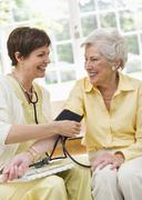 Nurse taking pulse of senior woman in nursing home Stock Photos