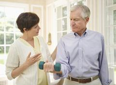 Stock Photo of Senior man lifting dumbbell, nurse assisting him