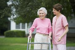 Senior woman walking with walker with help of nursing assistant Stock Photos