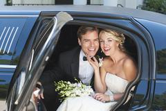 Stock Photo of Portrait of newly wed couple sitting in limousine