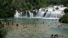 Shot of the tourists swimming in front of the waterfall in Krka national park Stock Footage