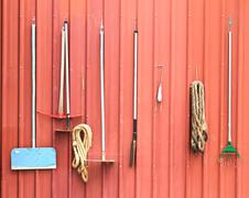 farm tools hang on red barn wall - stock photo
