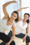 Two women exercising in gym - stock photo