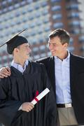 Father with teenage sun (16-17) at graduation ceremony - stock photo