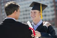 Father with teenage sun (16-17) at graduation ceremony Stock Photos