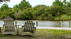 Weathered white adirondack chairs facing bay Stock Footage