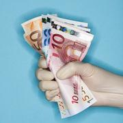 Hand in surgical glove holding banknotes Stock Photos