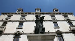 Close up shot of an old building`s facade with a statue in the midlle Stock Footage