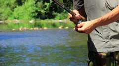 Man fishing on the river. Fisherman catching a fish in freshwaters. Reel Wind Up - stock footage