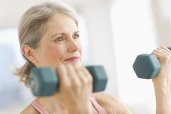 Stock Photo of Portrait of senior woman exercising with dumbbells in gym