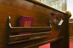 Close up of bible on wooden church pew Stock Photos