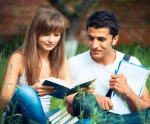 Two students studying in park on grass with book outdoors Stock Photos