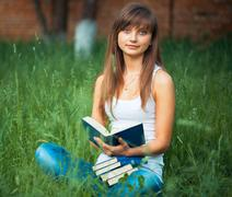 Young beautiful girl with book in the park Stock Photos