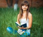 Stock Photo of young beautiful girl with book in the park