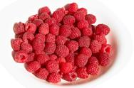 Stock Photo of raspberries on a plate over white