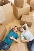 Couple lying among cardboard boxes during relocation Stock Photos