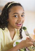 Stock Photo of Portrait of girl (12-13) eating dinner