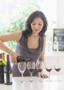 Woman purring red wine into wine glasses - stock photo