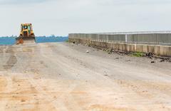 backhoe on dam crest - stock photo