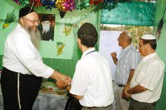 orthodox jews celebrate sukkot in a sukkah - stock photo