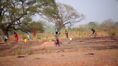 GAMBIA, 08 MARCH 2012: African women and children working in field Stock Footage