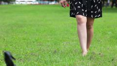 Woman in dress throwing off her shoes and walking on green grass barefoot Stock Footage