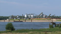 Sand mining along river Waal + zoom out river dike + cyclists Stock Footage
