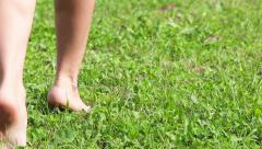Close-up view of female legs walking tiptoe on green field in summer - stock footage