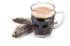 Glass mug with brown ale and dried fish - stock photo