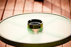 Black empty ashtray stands in the middle of a round glass table Stock Photos